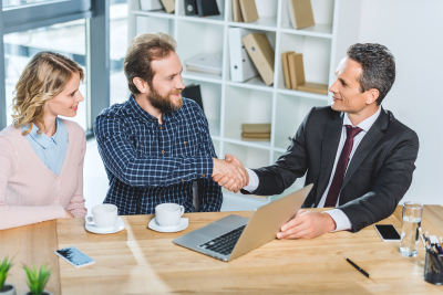 lawyer and client shaking hands at meeting in office